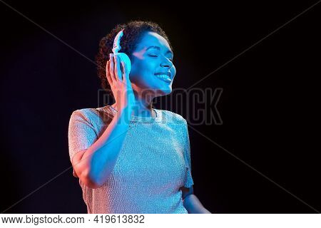 nightlife, technology and people concept - happy young african american woman in headphones listening to music and dancing in neon lights over black background
