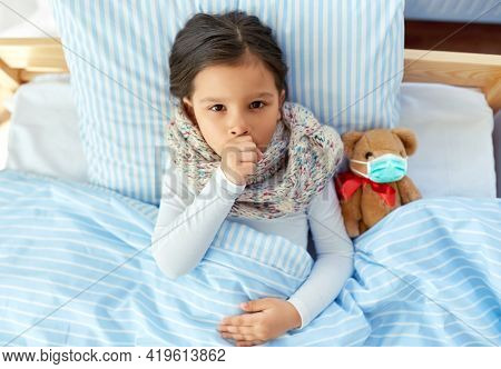 health, children and pandemic concept - sick coughing girl lying in bed with teddy bear toy wearing protective medical mask at home