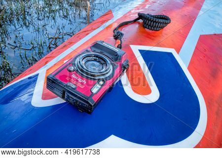 Fort Collins, CO, USA - May 4, 2021: Compact, waterproof Olympus Stylus Tough TG-5 camera on a wet deck of a stand up paddleboard by Mistral