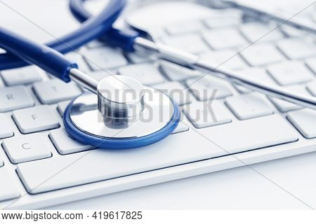 Close Up Of A Stethoscope On Computer Keyboard On White Desk. Online Health Care Or Telemedicine Con