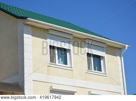 A Close-up Of A Stucco House With A Metal Green Roof, Rain Gutters, Soffit, Fascia, And Windows With