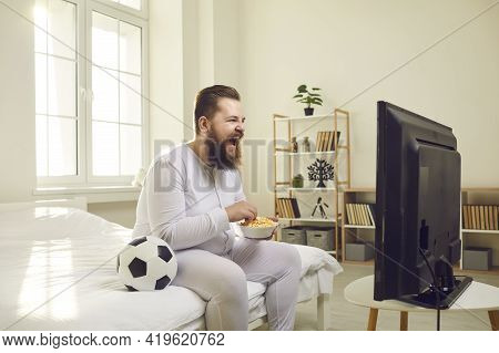 Side View Of Funny Bearded Fat Soccer Fan Watching Match On Tv At Home Sitting On Sofa.