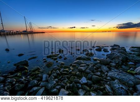 With Shoreline Rocks And Boats In The Marina To The Left, A Beautiful Sunset Is Reflected On The Wat