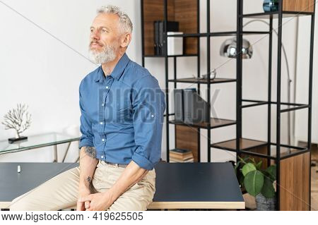 Tranquil Contemporary Middle Aged Businessman In Smart Casual Wear Leaned On The Desk And Looks Away