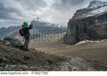 Banff, Canada - 08.30.2018: Man Taking A Photo Of Mt. Lefroy And Glacial Moraine Below At The End Of