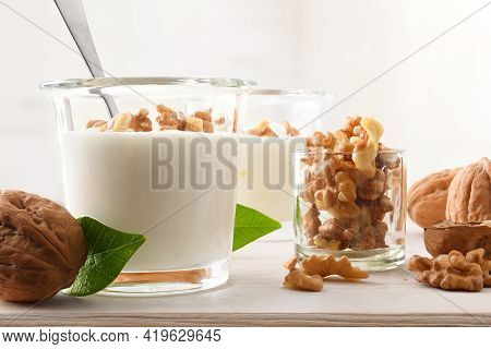 Walnuts Pieces On Natural Yogurt With Walnuts And Bowl With Walnuts On Wooden Kitchen Bench. Front V