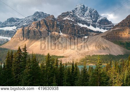Vulture Peak Towers Abovebow Lake In Banff National Park, Canada, Lit By Few Rays Of Light Under Dra