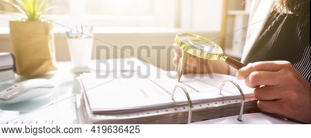 Fraud Investigation And Tax Audit. Investigator Or Auditor Using Magnifying Glass