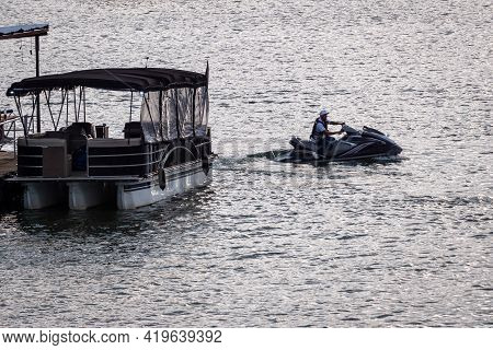 Guatapé, Antioquia, Colombia - April 3 2021: Latin Man Driving A Jetsky Near A Boat On The Lake At G