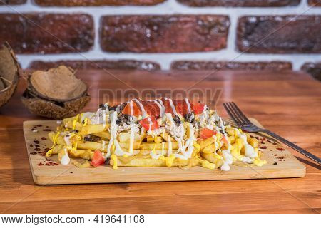 Delicious Crispy Canadian Putin On A Wooden Plank On A Wooden Table