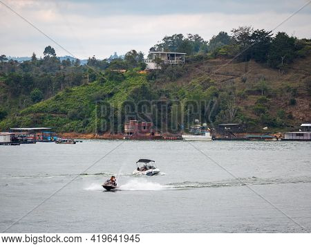Guatape, Antioquia, Colombia - April 3 2021: Latin Couple Driving A Jetsky In The Waters Of The Dam