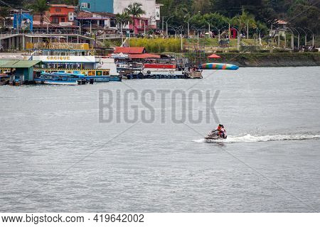 Guatapé, Antioquia, Colombia - April 3 2021: Latin Couple Driving A Jetsky In The Waters Of The Dam