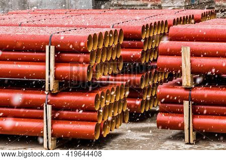 Pile Of Round Industrial Polyethylene Thermoplastic Pipes Storage Outdoor On A Construction Site Wit