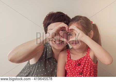 Asian Mother And Daugther Girl Making Heart Shape Gesture With Hands Over Eyes , Happy Volunteer ,do