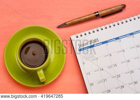 June 2021 - spiral desktop calendar with a pen and cup of coffee flat lay, time and business concept