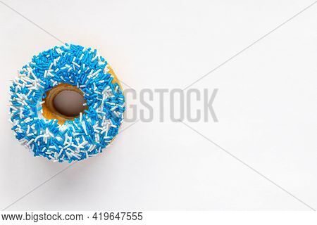 Donut With Blue And White Sprinkles On White Background With Copy Space.