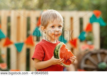 Happy Child Eating Watermelon In The Garden. Funny Kid Eating Watermelon Outdoors In Summer Park. Po