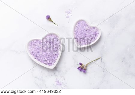 Lilac Spa Sea Salt In Bow Heart Shape On Marble Background. Daily Bodycare Concept, Natural Bath Pro