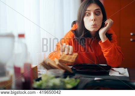 Hungry Girl Eating Bread Slice Before Dinner