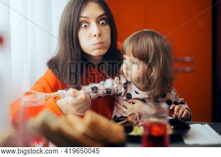 Hungry Mom Trying To Eat While Child Sits On Her Lap