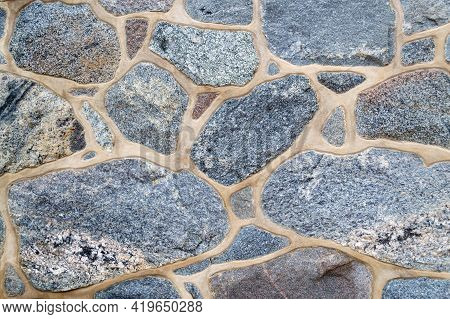 Fragment Of A Colored, Textured Stonewall. Wall Made Of Natural Stone And Cement. Bright Background.