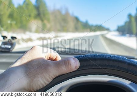 The Driver Hand Is On The Steering Wheel Of A Car That Is Driving On An Asphalt Road In Sunny Spring