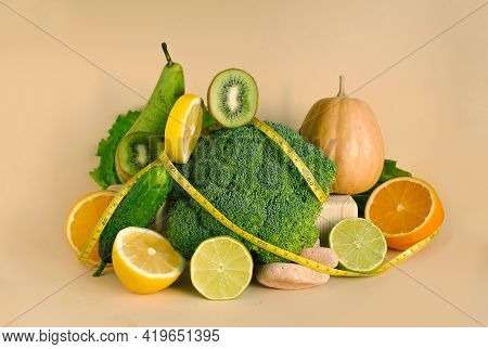 Vegetables And Fruits And A Measuring Tape. The Concept Of Losing Weight, Diet, Healthy Eating On Wh