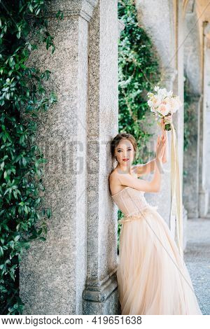 Bride In A Dress With A Bouquet Of Pink Flowers Is Leaning Against A Pillar With Her Arms Raised In