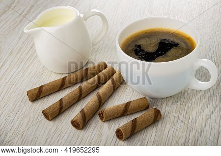 Pitcher With Milk, Brown Striped Wafer Rolls With Chocolate Filling, Halves Of Wafer Roll, Black Cof
