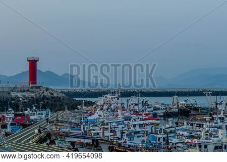 Daecheon, South Korea; April 25, 2021: Fishing Trawlers Moored At Dock Under Red Lighthouse At Sunse