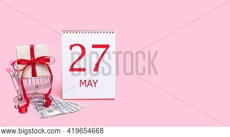 27th Day Of May. A Gift Box In A Shopping Trolley, Dollars And A Calendar With The Date Of 27 May On