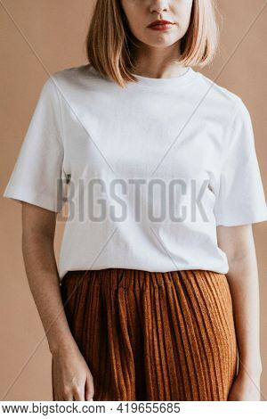 Short brown hair woman in a white tee and a brown skirt