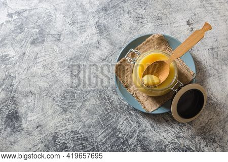 Ghee Or Clarified Butter In Jar And Wooden Spoon On Gray Table. Top View. Copyspace. Ghee Butter Hav