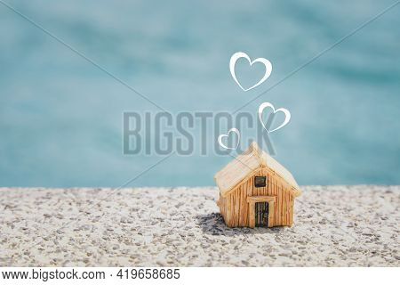 Miniature House And  Heart Shape On Concrete Floor With Blurred Blue Background, Copy Space, Home Sw