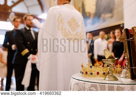 Wedding Ceremony In An Orthodox Church. The Groom, The Best Man And The Priest In A Cassock Stand In