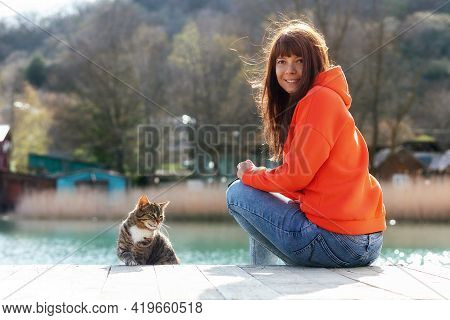 A Female Volunteer Sits On A Bench Near A Stray Hungry Cat. A Shelter Worker Takes Care Of The Stree