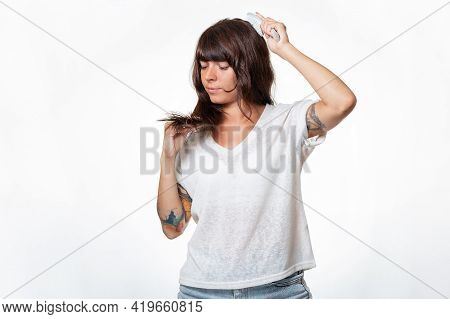 Portrait Of A Young Tattooed Woman Combs Her Hair And Looks At The Split Ends In Frustration. White