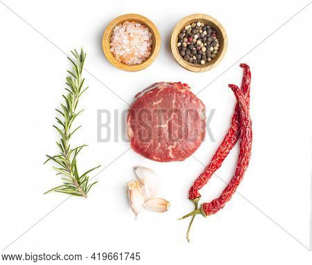 The raw beef meat steak with garlic, rosemary, salt and pepper isolated on white background.