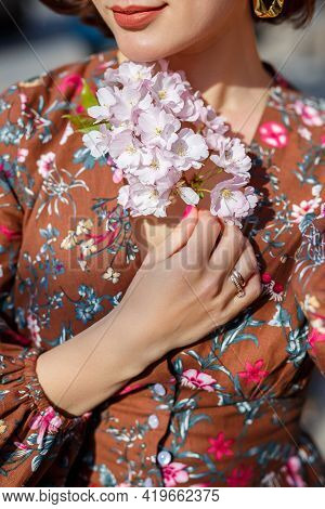 Portrait Of A Gentle Woman Against The Background Of Sakura Flowers. Walk In The Blossoming Sakura G