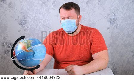 Man Is Sad About The Illnesses On The Plan And The Lack Of Travel. Male Looks Globe In Protective Ma