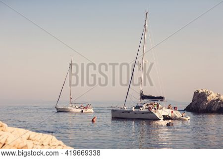 Hvar, Croatia - August 28, 2007; White Yachts With Lowered Sails In A Secluded Cove Off The Coast Of