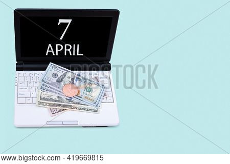 7th Day Of April. Laptop With The Date Of 7 April And Cryptocurrency Bitcoin, Dollars On A Blue Back