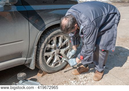 Replacing The Wheel On The Road By The Driver. Replacing Summer Tires With Winter Tires With A Handy