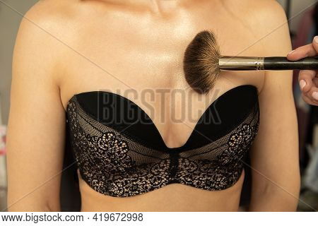 Female Breasts In Black Lace Lingerie, Makeup Brush In Hands Of Make-up Artist Applies Highlighter B