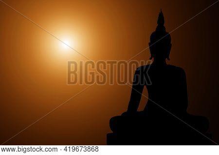 Silhouette Buddha On Golden Sunset Background. Sitting Buddha