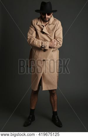 Exhibitionist In Coat And Hat On Black Background
