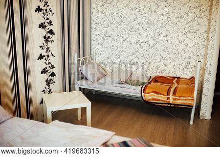 Made-up Bed In The Apartment. Single Cozy Bed. Minimalistic Interior Of The Apartment In Bright Colo