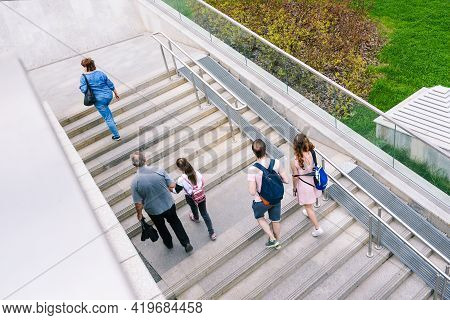 A Group Of People Are Going Down The Stairs. Concrete Staircase With Railings, Ramp And Green Grass.