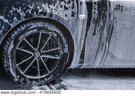 The Front Wheel And Part Of The Body Of A Black Car Covered With Dripping Foam From The Detergent At