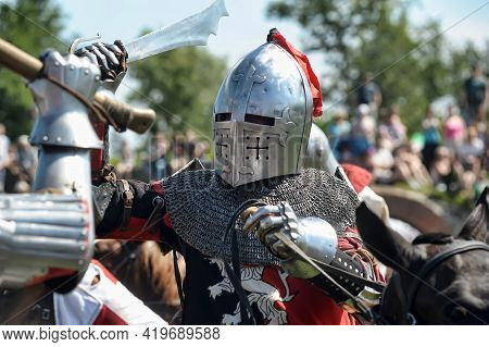 Knight On Horseback In Military Armor At The Knightly Tournament On The Reconstruction